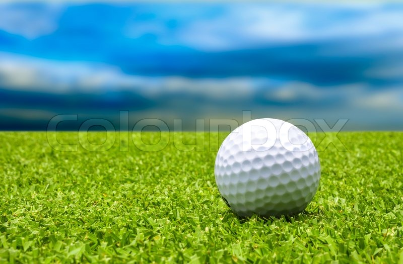 Golf ball on tee with blue sky, stock photo