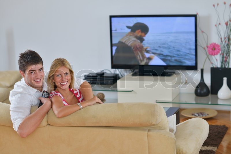 Relaxed young couple watching tv at home in bright living room, stock photo