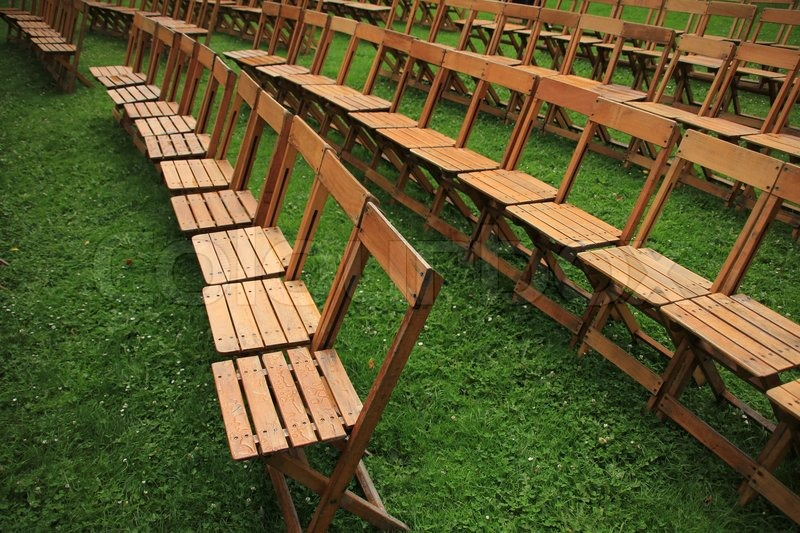 Folding chairs stand in the grass in the open air waiting for the coming people for the next performance, stock photo