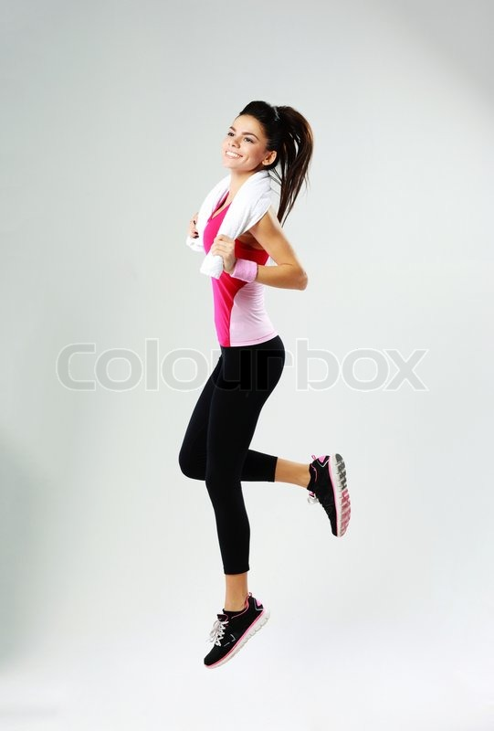 Young cheerful sport woman with towel jumping on gray background, stock photo