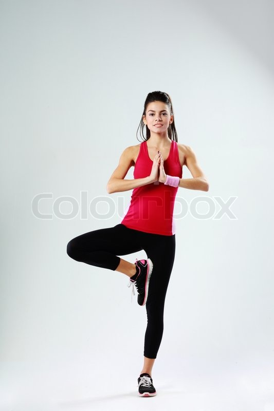 Young sport woman meditating while standing on one leg on gray background, stock photo