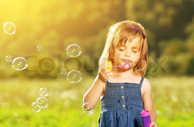 Девочка выдувает мыльные пузыри