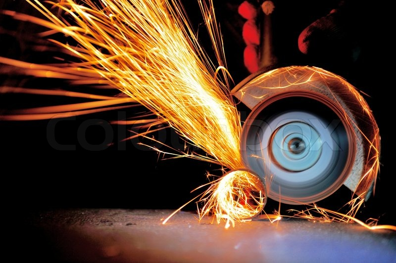 Worker cutting metal with grinder. Sparks while grinding iron, stock photo