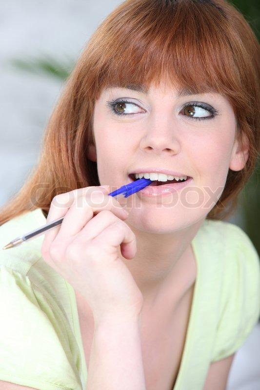 Stock Bild von 'Junge Frau, die auf einen Stift kauen'