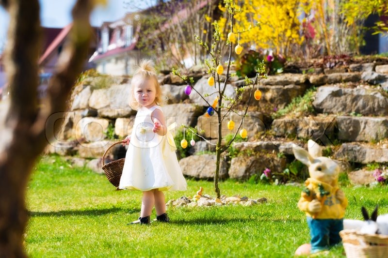 Little girl on an easter egg hunt on a meadow in spring she little girl on an easter egg hunt on a meadow in spring she holding a basket or easter basket stock photo colourbox negle Choice Image