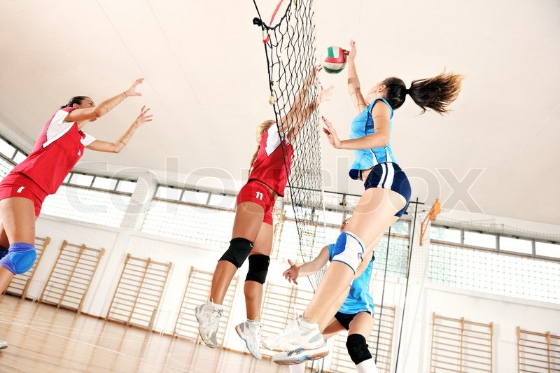 Volleyball game sport with group of young beautiful girls indoor in sport arena, stock photo