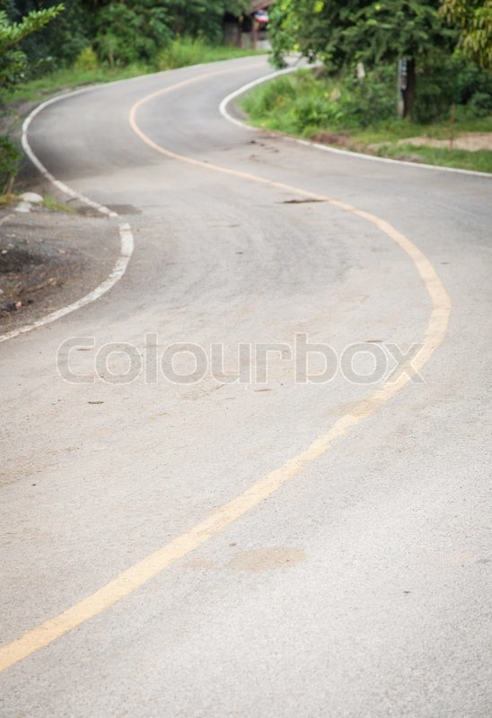 Curved road is curved, not much. The side of the road with a tree, stock photo