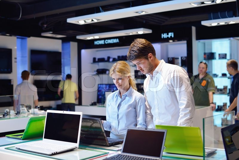 People in consumer electronics retail store looking at latest laptop, television and photo camera to buy, stock photo