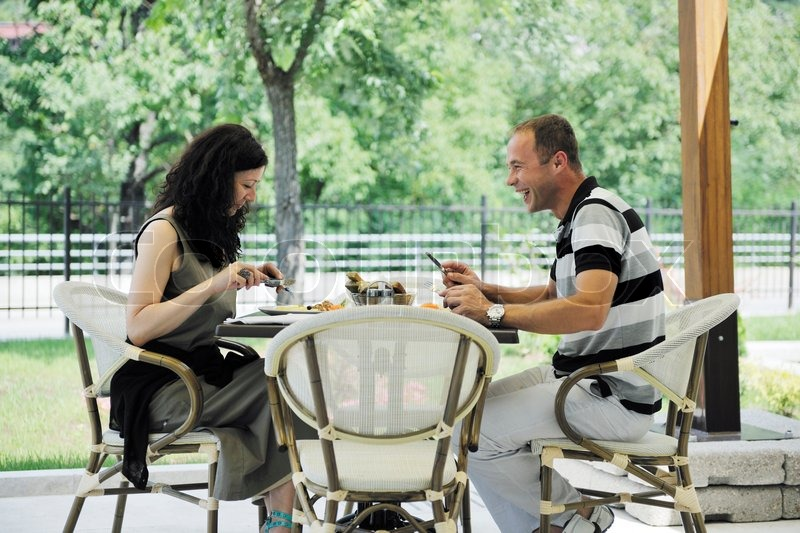 Happy young couple eat fresh food at beautiful restaurant restaurant outdoor, stock photo