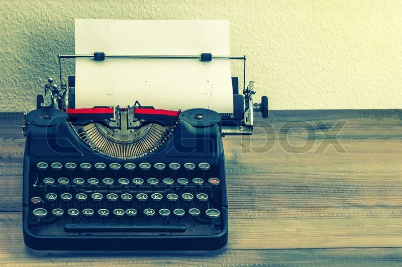 Retro typewriter with white paper page on wooden table. vintage style toned picture, stock photo