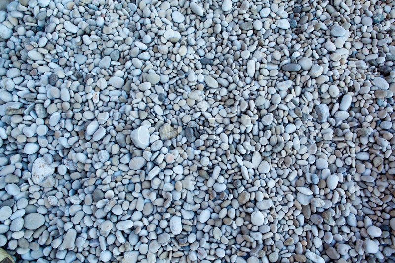 Naturally polished white rock pebbles background on beach, stock photo