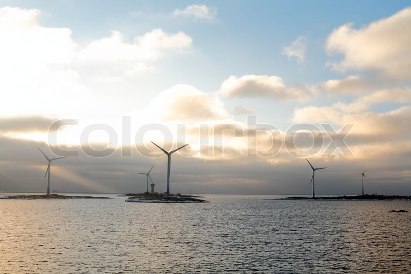 Wind farm on small islands in Baltic Sea in dramatic light over open sea with sun breaking through dark clouds in horizon , stock photo
