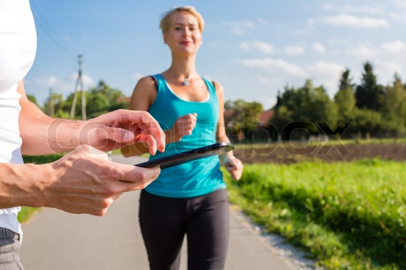 Woman doing jogging or outdoor running sport for fitness on rural street, the trainer stopping her time with app on tablet computer, stock photo