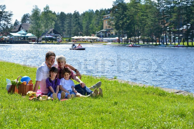 Happy young family playing together with kids and eat healthy food in a picnic outdoors, stock photo