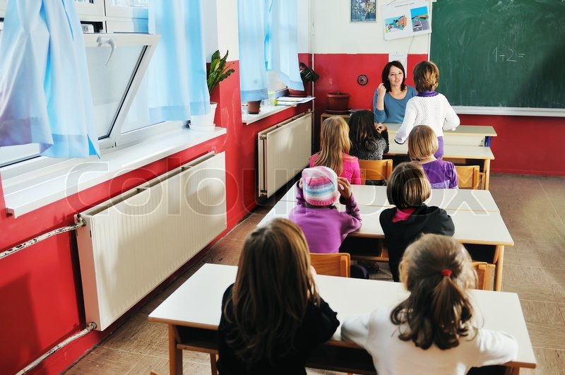 Happy young teacher woman at elementrary school teaching and giving leassons to group of young smart children, stock photo