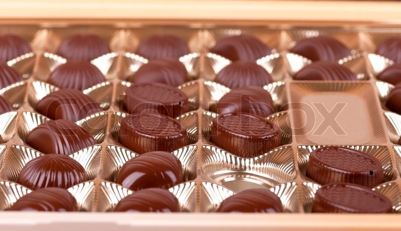 Chocolate sweets lie in the cells of the boxes in a number of, stock photo