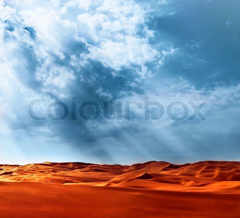 Beautiful landscape of Liwa desert, United Arab Emirates, Abu Dhabi, orange hot sand, blue cloudy sky, beauty of nature concept, stock photo
