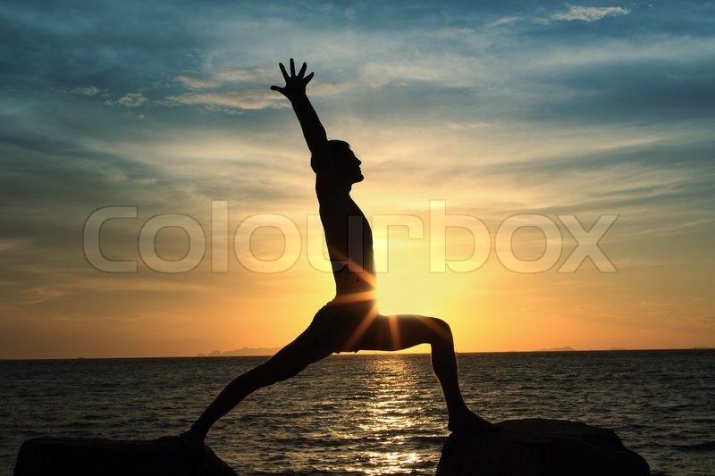 Silhouette of perfect body man act yoga on the rock with sea sunset background, stock photo