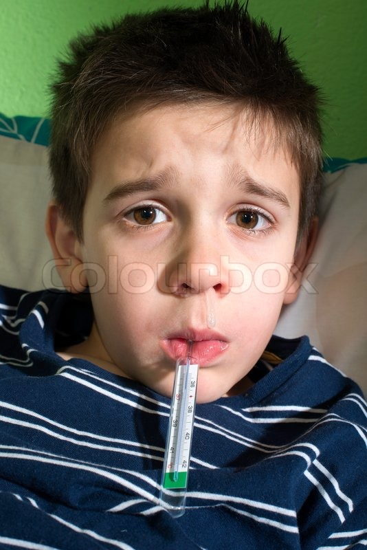 Sick child in bed. Measuring the temperature with a thermometer, stock photo