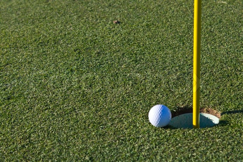 Golf ball almost in the hole, stock photo