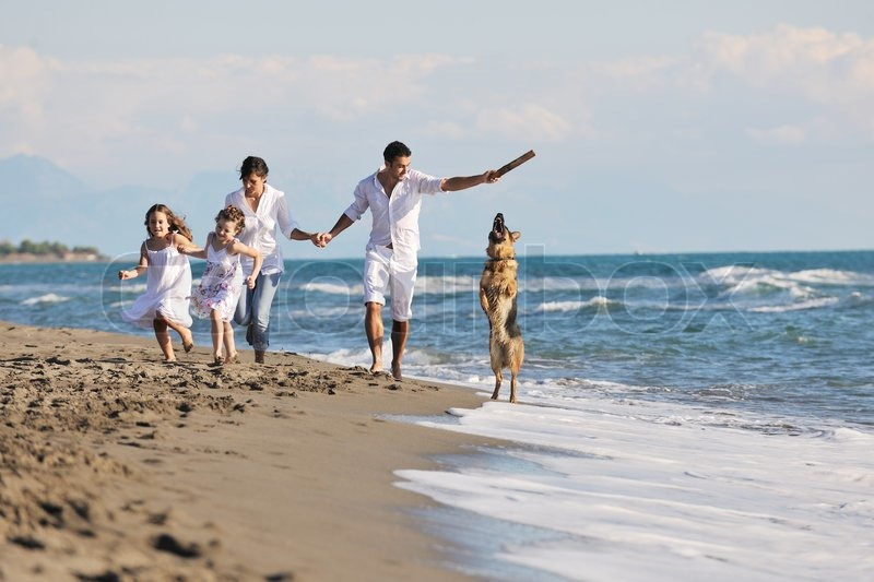 Happy young family in white clothing have fun and play with beautiful dog at vacations on beautiful beach, stock photo