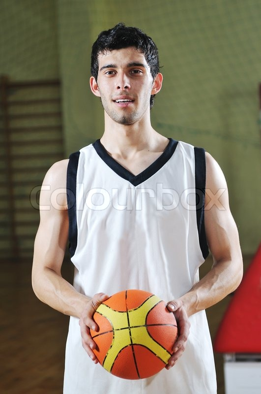 One basket ball game player standing in sport gym with ball, stock photo