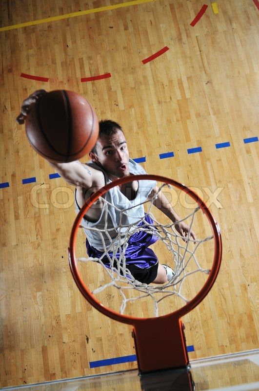One healthy young man play basketball game in school gym indoor, stock photo