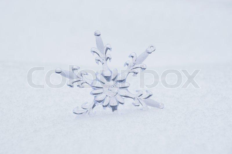 Snowflake in a white snow, stock photo