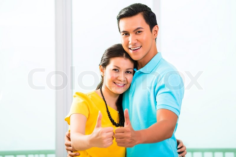 Young Asian handsome couple in apartment with city view showing thumbs up |  Stock Photo | Colourbox