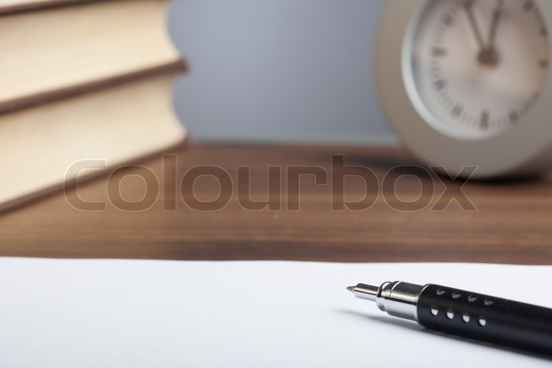 Black bullet pen, stack of books, clock and an empty sheet of paper, stock photo