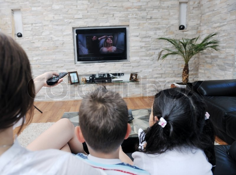 Happy young family wathching flat tv at modern home indoor, stock photo
