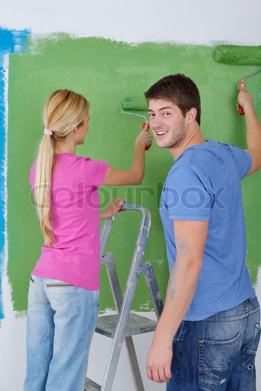 Happy young couple paint in green and blue color white wall of their new home, stock photo