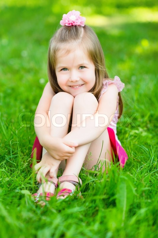 cute little girl with long blond hair sitting on grass in