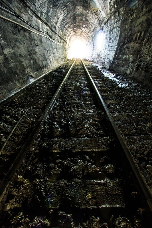 Light at the end of railroad tunnel. Natural lighting, stock photo
