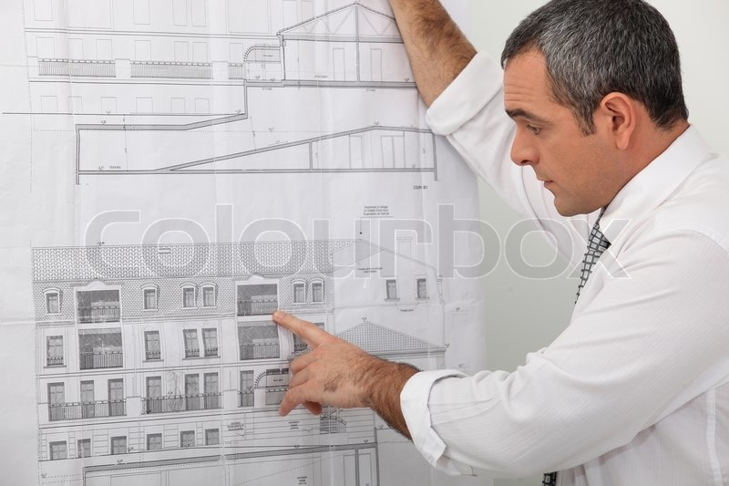 Architect examining a blueprint in detail, stock photo