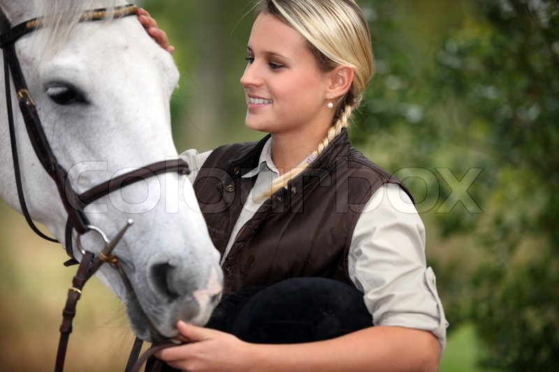Stock image of 'Young lady stroking her horse'