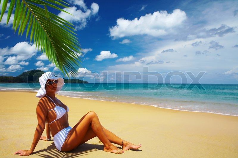 Stock image of 'view of nice woman lounging on tropical beach in white panama and bikini'