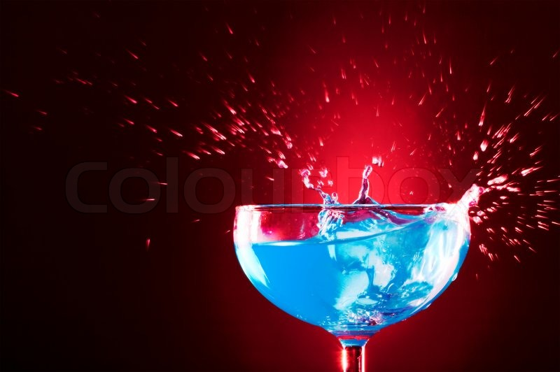 Stock image of 'view of  cocktail glass with blue Curacao splashing over'