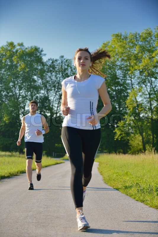Stock image of 'Young couple jogging in park at morning. Health and fitness concept'