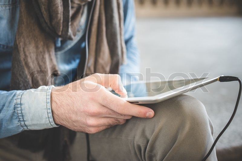 Stock image of 'close up of man hands using tablet outdoors'