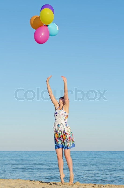 Stock image of 'Young woman with colorful balloons over sea.'