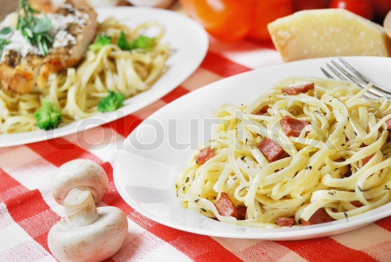 Stock image of 'Pasta carbonara in the white plate on the wooden table'