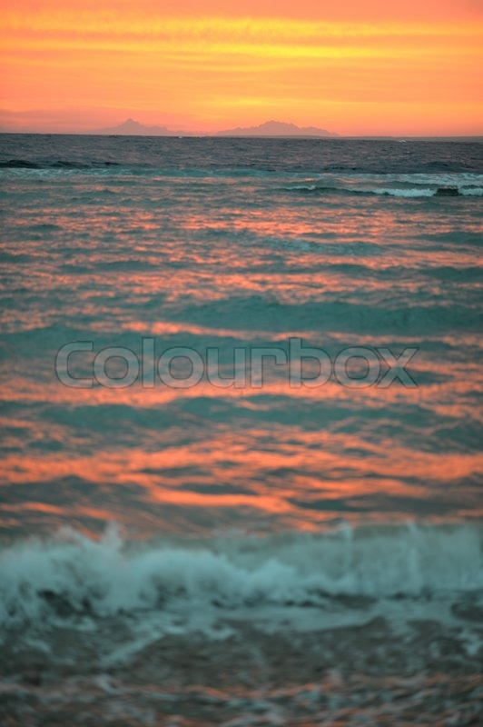 Stock image of 'Beautiful sea waves on the background of the rising sun'