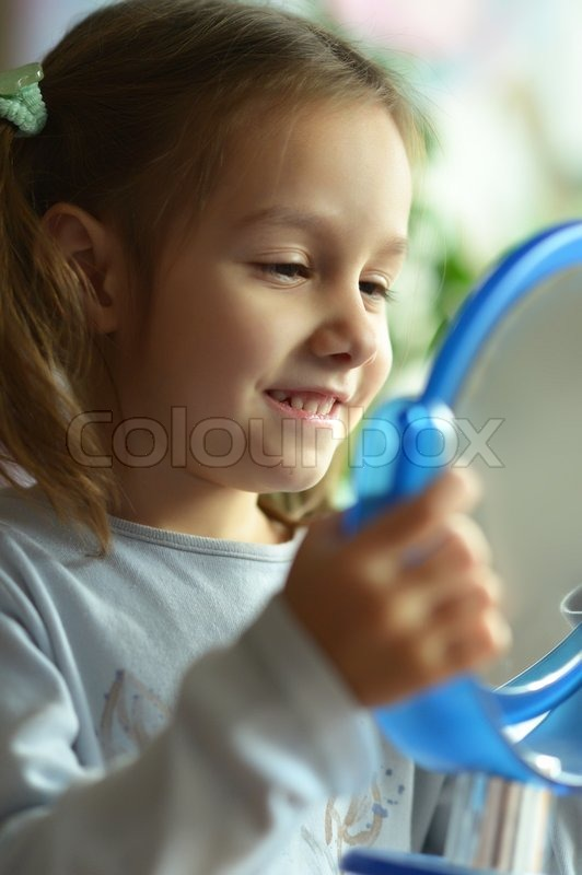 Stock image of 'Portrait of a little girl with a mirror at home'