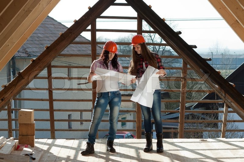 Two young women workers standing on under construction roof, and control building in accordance with drawing, stock photo