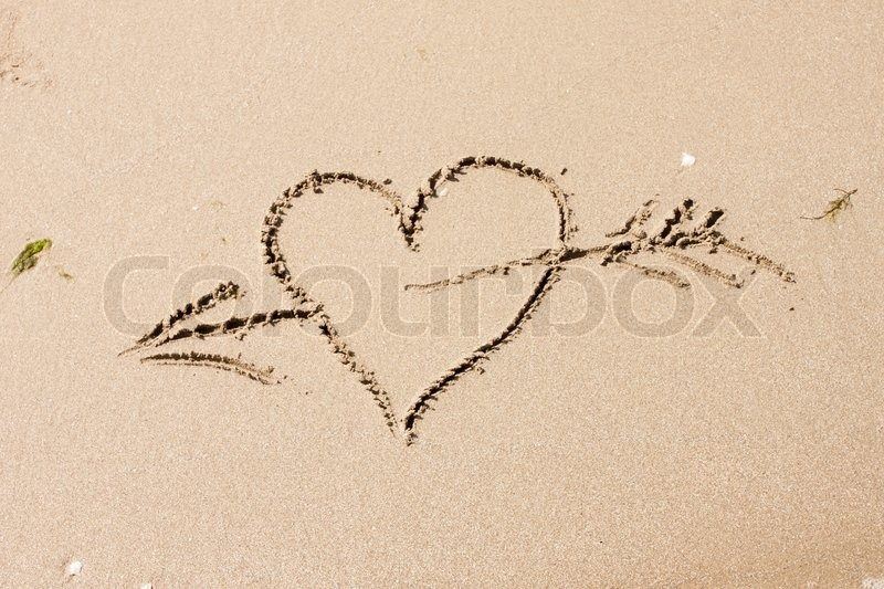 Stock image of 'heart with an arrow written on the sandy beach with wave'