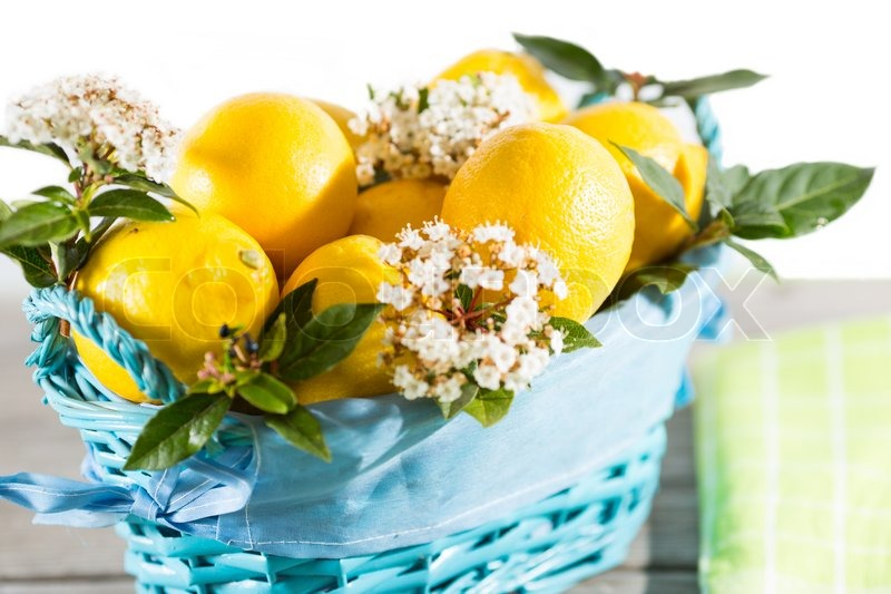 Stock image of 'Fresh lemons in a basket decorated with green leaves'