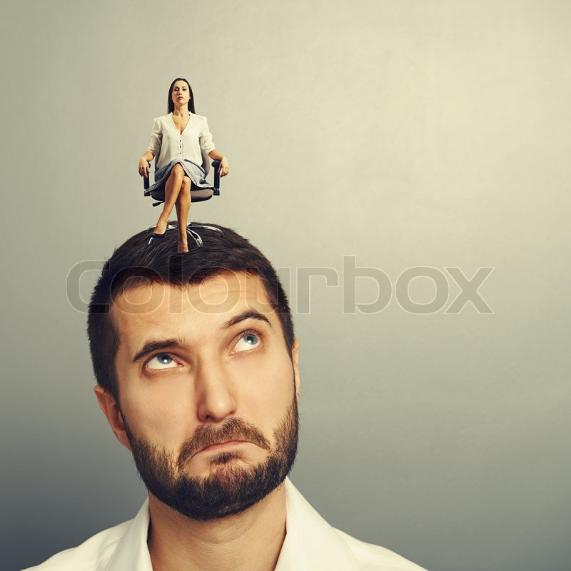 Stock image of 'thoughtful man looking at strict woman on his head over dark background'