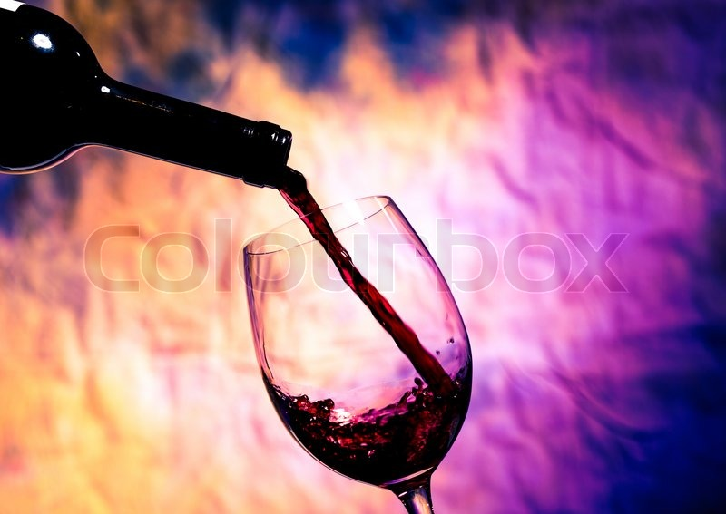 Stock image of 'Red Wine Poured into Wineglass on background grunge bright multicolored'