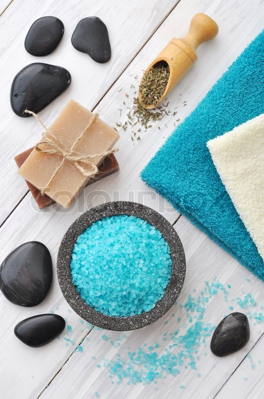 Stock image of 'Spa composition with blue sea salt and massaging stones on white wooden background'